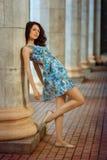 Piękna młoda brunetki kobieta stoi blisko kolumny zdjęcie royalty free