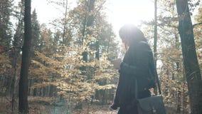 Piękna Młoda brunetki kobieta Używa Smartphone W jesień parku Dziewczyny odprowadzenie W lesie W spadku, stylu życia pojęcie zdjęcie wideo