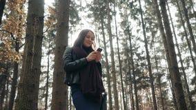 Piękna Młoda brunetki kobieta Używa Smartphone W jesień parku Dziewczyny odprowadzenie W lesie W spadku, stylu życia pojęcie zbiory