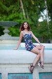 Piękna młoda brunetki kobieta z falistym włosy w krótkiej sukni siedzi na krawędzi fontanny w parku fotografia stock