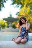 Piękna młoda brunetki kobieta z falistym włosy w krótkiej sukni siedzi na krawędzi fontanny w parku obraz royalty free