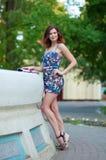 Piękna młoda brunetki kobieta z falistym włosy w sukni krótkich stojakach blisko fontanny w parku fotografia royalty free