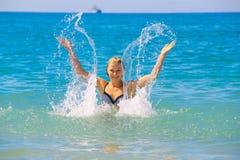 Piękna młoda caucasian kobieta bryzga wodę w morzu na letnim dniu obraz stock