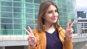 Piękna młoda caucasian kobieta ono uśmiecha się z zwycięstwo znakiem plenerowym w mieście zdjęcie wideo