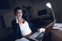 Piękna młoda ciężarna dziewczyna pracuje na laptopie Ciężarny w ciemnym biurze fotografia stock