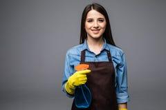 Piękna młoda cleaner kobieta z detergentem w ręce odizolowywającej na popielatym Obrazy Stock
