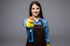 Piękna młoda cleaner kobieta z detergentem w ręce odizolowywającej na popielatym Fotografia Stock
