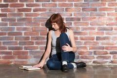 Piękna młoda czerwona włosiana kobieta w cajgach z książkowym obsiadaniem na podłogowym pobliskim ściana z cegieł Attentively czy Fotografia Stock