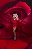 Piękna młoda dama w czerwieni sukni stojakach na kwiacie wzrastał zdjęcia royalty free