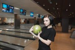Piękna młoda dziewczyna bawić się w kręgle alei z zieloną piłką w ona ręki Odpoczynek po bawić się kręgle Obraz Royalty Free
