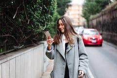 Piękna młoda dziewczyna bierze fotografie na smartphone Zdjęcia Royalty Free