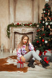 Piękna młoda dziewczyna blisko choinki z prezentami zdjęcie stock