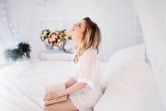 Piękna młoda dziewczyna czyta wewnątrz książce coś śmiesznego Atrakcyjna kobieta, jej sypialnia obraz stock
