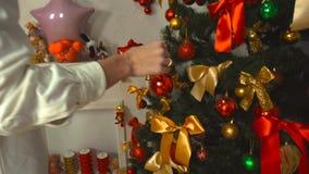 Piękna młoda dziewczyna dekoruje choinki z jaskrawą czerwoną piłką zbiory wideo