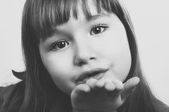 Piękna młoda dziewczyna dmucha buziaka bw Zdjęcia Stock