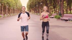 Piękna młoda dziewczyna i mężczyzna trenuje bieg w parku, zwolnione tempo zbiory