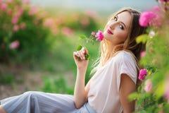 Piękna młoda dziewczyna jest ubranym przypadkowych ubrania ma odpoczynek w ogródzie z menchii okwitnięcia różami Obrazy Royalty Free