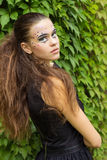 Piękna młoda dziewczyna na tle liście w jesień dniu na ulicie z fantazi makeup w czarnej sukni Fotografia Royalty Free