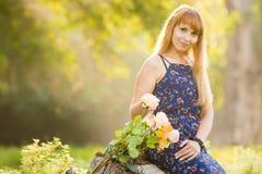 Piękna młoda dziewczyna na tle pogodny zamazany greenery, kłamstwa obok bukieta róże fotografia stock