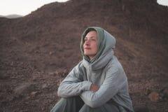 Piękna młoda dziewczyna odpoczynkowa i ono uśmiecha się w pustyni Zdjęcia Royalty Free