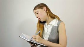 Piękna młoda dziewczyna opowiada telefonem komórkowym i pisze notatkach notatnik zbiory