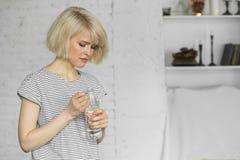 Piękna młoda dziewczyna otwiera butelkę spokojna woda Zdjęcie Stock