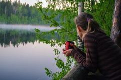 Piękna młoda dziewczyna pije filiżankę kawy lub herbaty grzać up Portret kobiety atrakcyjny zamyślenie patrzeje out nad jeziorem  Fotografia Royalty Free