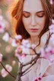Piękna młoda dziewczyna pod kwiatonośnym różowym drzewem zdjęcia royalty free