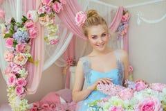 Piękna młoda dziewczyna przy błękitną suknią z kwiatami w dekorującej sypialni Zdjęcie Stock