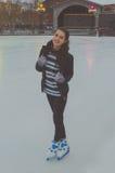 Piękna młoda dziewczyna przy lodowiskiem w zimie, jazda na łyżwach, fotografia royalty free