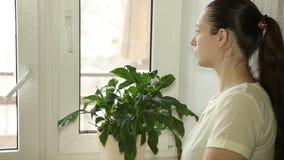 Piękna młoda dziewczyna przyglądająca out okno zbiory