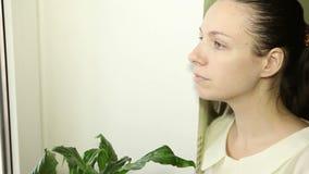 Piękna młoda dziewczyna przyglądająca out okno zbiory wideo