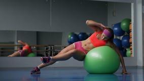 Piękna młoda dziewczyna robi ćwiczeniom z dysponowaną piłką przy sporta gym zbiory