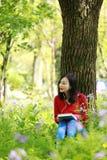 Piękna młoda dziewczyna Słucha muzyka na telefonie komórkowym podczas gdy siedzący pod gigantycznym dębem zdjęcia royalty free