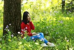 Piękna młoda dziewczyna Słucha muzyka na telefonie komórkowym podczas gdy siedzący pod gigantycznym dębem fotografia royalty free