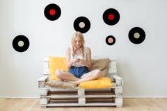Piękna młoda dziewczyna słucha muzyka siedzi na c w domu Obrazy Royalty Free
