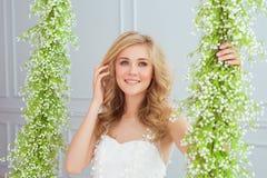 Piękna młoda dziewczyna siedzi na huśtawce z kwiatem Obraz Royalty Free