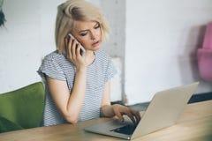Piękna młoda dziewczyna siedzi przed laptopem i mówi na telefonie Zdjęcie Stock