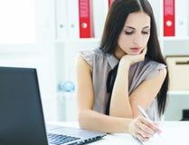 Piękna młoda dziewczyna siedzi przy biurem robi notatkom Biznes, wekslowy rynek, oferta pracy, analityka bada, znakomity zdjęcia stock