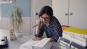 Piękna młoda dziewczyna siedzi przy czytaniem i stołem w domu w szkłach książka homework zdjęcie wideo