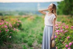 Piękna młoda dziewczyna siedzi w ogródzie z menchii okwitnięcia różami jest ubranym przypadkowych ubrania Zdjęcie Stock