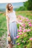 Piękna młoda dziewczyna siedzi w ogródzie z menchii okwitnięcia różami jest ubranym przypadkowych ubrania Obrazy Royalty Free