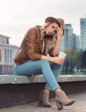 Piękna młoda dziewczyna siedział puszek na krawężniku Obraz Royalty Free