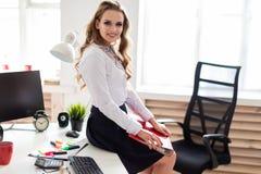 Piękna młoda dziewczyna siedział puszek na stole w biurze i trzymał falcówkę z dokumentami obrazy royalty free