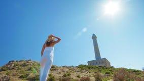 Piękna młoda dziewczyna, spojrzenia przy latarnią morską w słomianym kapeluszu, Pojęcie: odtwarzanie, piękny widok, wolność, podr zdjęcie wideo