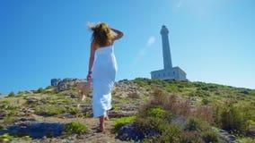 Piękna młoda dziewczyna, spojrzenia przy latarnią morską w słomianym kapeluszu, Pojęcie: odtwarzanie, piękny widok, wolność, podr zbiory