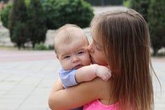 Piękna młoda dziewczyna trzyma jej nowonarodzonego brata i całuje on tenderly fotografia stock