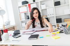 Piękna młoda dziewczyna trzyma pióro blisko jej twarzy i dosięga dla jaskrawych majcherów siedzi przy biurowym biurkiem Zdjęcia Stock