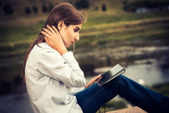 Piękna młoda dziewczyna używa cyfrową pastylkę Fotografia Royalty Free