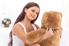 Piękna młoda dziewczyna w łóżkowym patrzeje misiu Fotografia Stock